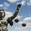 Image of lady justice with scales against a blue sky